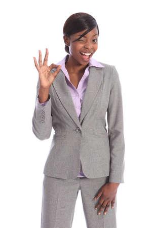 businesswoman suit: Signo positivo por la mano bien joven y bella mujer de negocios �tnicos africanos americanos con una gran sonrisa y gui�ando un ojo.