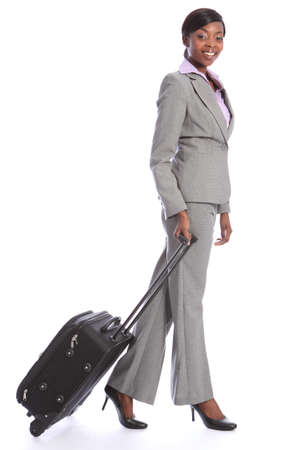 First class business travel for a happy beautiful young african american woman wearing a smart grey suit, walking and pulling her suitcase. Stock Photo - 10252596