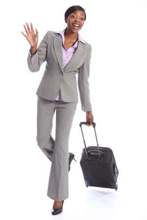 Negocios de primera clase de viaje para una feliz bella joven mujer afroamericana llevaba un traje gris inteligente, agitando en saludo mientras tira su maleta.