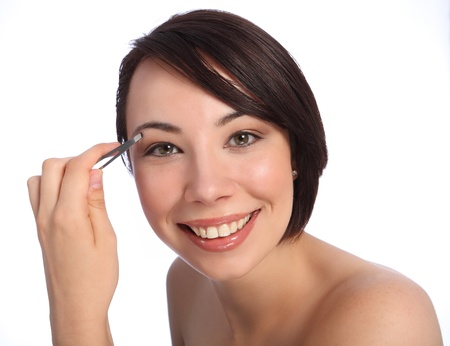 Happy smile from beautiful young caucasian woman using tweezers to pluck her eyebrow as part of make up routine. Taken against a white background. photo