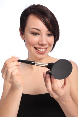 flawless: Big happy smile from beautiful young caucasian woman with clear flawless skin applying make up from cosmetics compact using blusher brush. Taken against a white background.