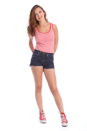 denim shorts: Pretty young teenager school girl 16, with long brown hair wearing blue denim cut off shorts and red and white vest with red shoes. She has a big happy smile. Studio shot against white background. Stock Photo