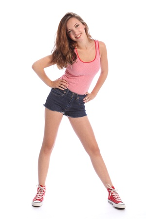 girl in shorts: Beautiful young teenager school girl 16, with long brown hair wearing blue denim cut off shorts and red and white vest with red shoes. She has a big happy smile. Studio shot against white background. Stock Photo