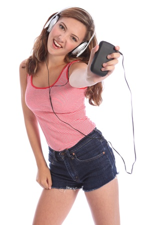 Enjoying music on her headphones from mobile smart phone, for a beautiful young teenager school girl 16, with long brown hair wearing a red and white vest. Studio portrait against white background. photo