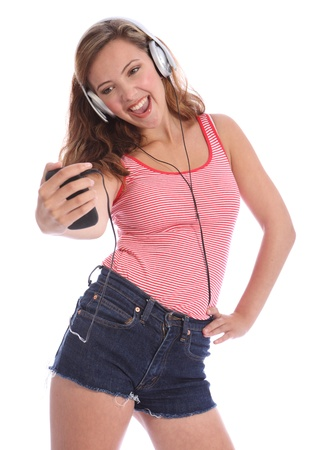 child singing: Enjoying singing to music on her headphones from cell phone, for a beautiful young teenager school girl 16, with long brown hair wearing a red and white vest. Studio portrait against white background. Stock Photo