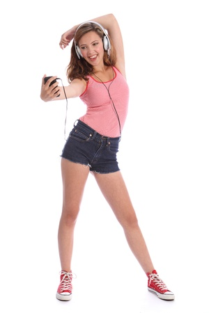 denim shorts: Pretty teenage girl with long legs wearing denim cut off shorts, having great fun listening to music on her cell phone. Girl is wearing silver headphones.