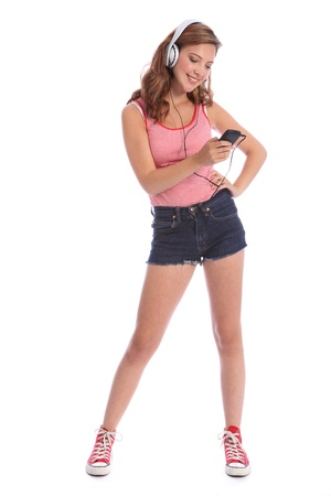 denim shorts: Beautiful caucasian teenage girl with long legs wearing denim cut off shorts, using her mobile phone listening to music with silver headphones.
