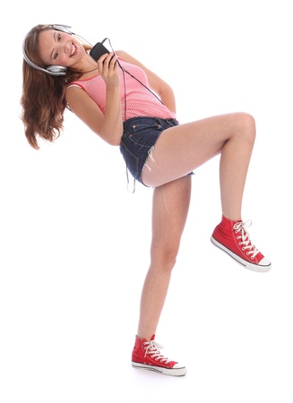 secondary: Happy beautiful caucasian teenage girl with long legs wearing denim cut off shorts, using her mobile phone listening and dancing to music with silver headphones.