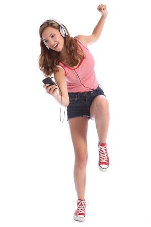 Happy beautiful caucasian teenage girl with long legs wearing denim cut off shorts, using her mobile phone listening and dancing with energy to music with silver headphones.