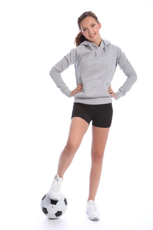 indoor soccer: Athletic soccer player teenage girl with happy smile wearing sports clothes, standing in casual pose with a ball under her foot. Full length shot against white background.