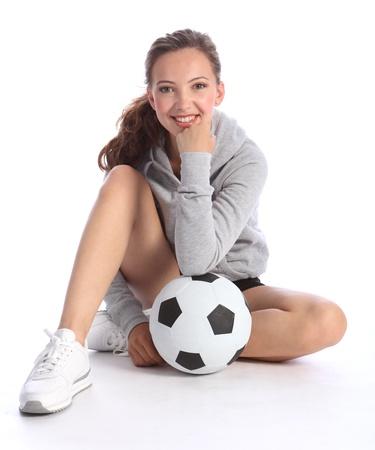Teenage girl footballer sitting on floor relaxing with big smile, holding ball wearing grey hoodie. photo