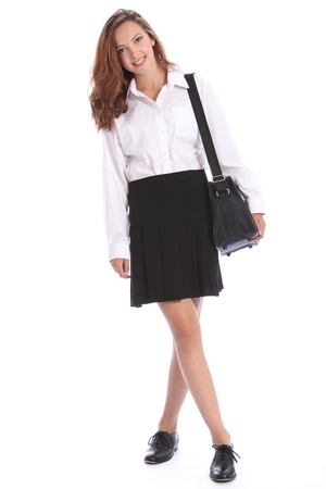 uniform skirt: Happy smile from beautiful teenage secondary school student girl wearing black and white school uniform, bag over her shoulder.