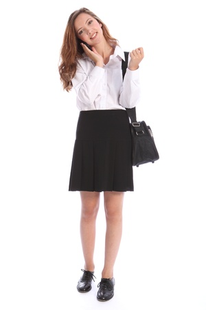Happy smile from young teenage secondary school student girl, talking to friends on mobile phone. She is wearing black and white school uniform. Stock Photo - 10382695