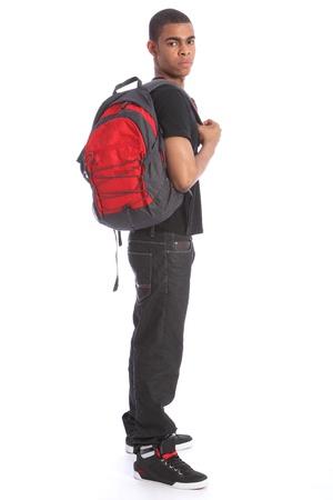 Adolescente estudiante afroamericano con vaqueros y camiseta, de pie con una mochila escolar. Foto de archivo