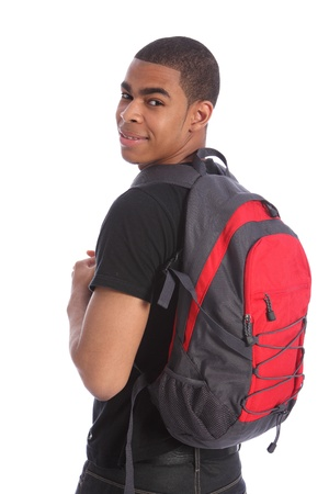 Handsome young black teenage student boy looking back over his shoulder wearing red rucksack, ready for school with a smile. photo