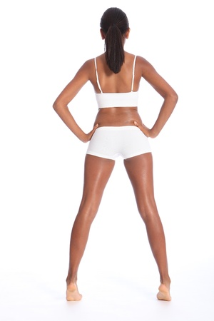 girls underwear: Rear view of a beautiful healthy young african american woman wearing white sports underwear, standing against white background showing off fit body. Stock Photo