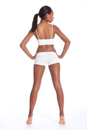 knickers: Behind view of a beautiful healthy young african american woman wearing white sports underwear, standing against white background showing off fit body.