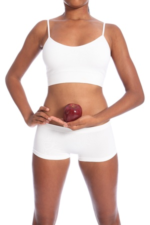 Healthy body of young african american woman wearing white sports underwear, holding red apple fruit in one hand, standing against white background. Stock Photo - 10389750