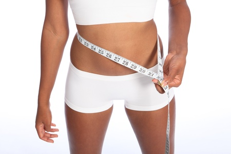 Healthy torso of young african american woman wearing white sports underwear, checking diet weight loss on waist with tape measure, standing against white background. Stock Photo - 10389749