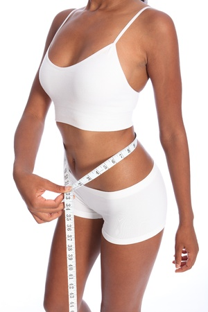 Healthy torso of young african american woman wearing white sports underwear, checking diet weight loss on waist with tape measure, standing against white background. photo