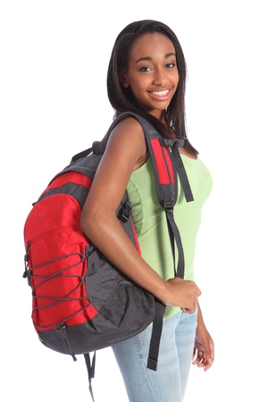 Pretty young African American teenager school girl, with long black hair wearing green t-shirt and red school backpack with happy smile. Studio shot against white background.