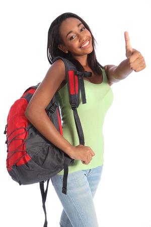 Los pulgares para arriba feliz �xito de muy joven africana chica americana de la escuela adolescente, con el pelo largo negro con camiseta verde y mochila escolar de color rojo, con una hermosa sonrisa. Foto de archivo