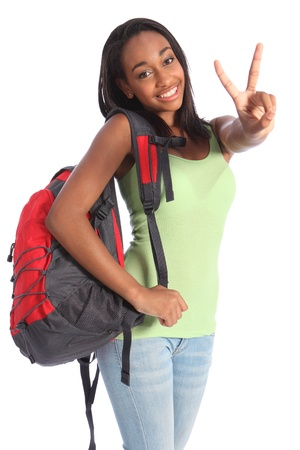 victory stand: V for victory success by pretty young African American teenager school girl, with long black hair wearing green t-shirt and red school backpack with beautiful smile.