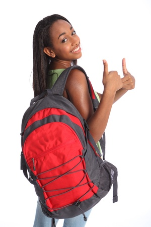 Positive thumbs up success for pretty young African American teenager school girl, with long black hair wearing green t-shirt and red school backpack with beautiful smile.