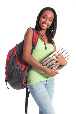 Chica de estudiante bastante joven adolescente afroamericano con gran sonrisa llevaba mochila Roja y celebraci�n de libros escolares. Ella tiene el pelo largo y negro y vestido con chaleco verde y pantalones vaqueros. Foto de archivo
