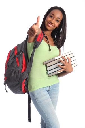 african student: Thumbs up per l'istruzione di successo da giovane e graziosa ragazza afro-americana studente adolescente con grande sorriso bella che porta zaino rosso e tiene i libri di scuola. Archivio Fotografico