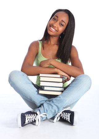Time for education from pretty young African American teenager school girl student with big beautiful smile, sitting cross legged on floor wearing blue jeans and vest holding school books. Stock Photo - 10389752