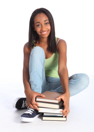 Education time for pretty young African American teenager school girl student with big beautiful smile, sitting on floor wearing blue jeans and vest holding school study books. Stock Photo - 10389751