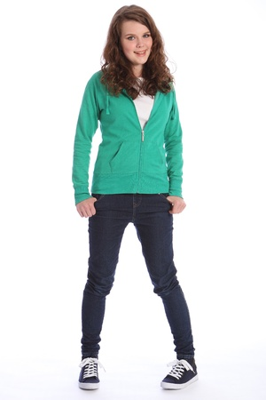 Happy smile from pretty teenager school girl with long brown hair, wearing dark blue jeans and a green hoodie sweater.