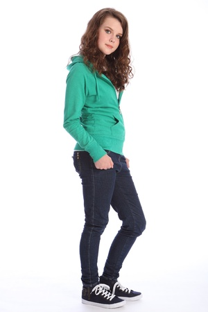 teen girl brown hair: Happy smile from pretty teenager school girl with long brown hair, wearing dark blue jeans and a green hoodie sweater.
