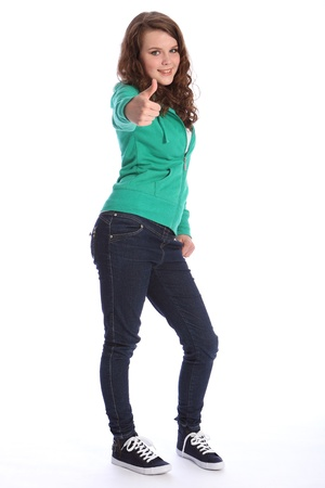 Happy smile from pretty teenager school girl with long brown hair, giving a thumbs up positive hand sign. She is wearing dark blue jeans and a green hoodie sweater. Stock Photo - 10401730