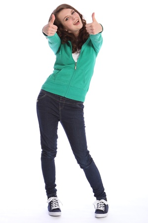 Two thumbs up for big success by happy pretty teenager school girl with long brown hair. She is wearing dark blue jeans and a green hoodie sweater.