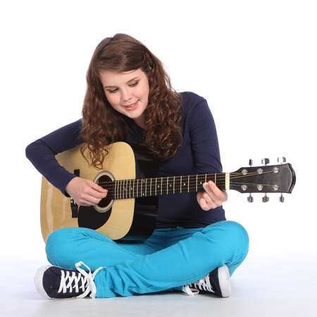 Happy concentration from pretty teenager girl sitting on floor playing music on acoustic guitar. She is wearing bright blue trousers and navy top.