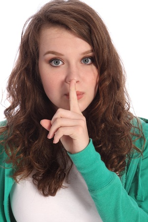Secret hand sign by cute teenager school girl with long brown hair and big blue eyes. She has a finger over her lips indicating quiet or not speaking. Stock Photo - 10429862