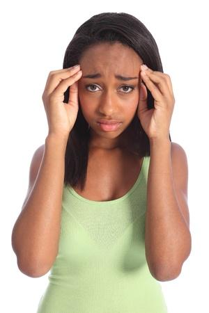 lesionado: Dolor de cabeza doloroso para ni�a afro-americana, sosteniendo sus manos a las sienes con dolor que muestra en su rostro. Dispar� contra el fondo blanco. Foto de archivo