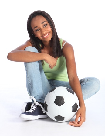 Beautiful young African American teenage school girl soccer player, sitting on the floor with a football. Girl wearing blue jeans and casual vest and has a big happy smile. photo