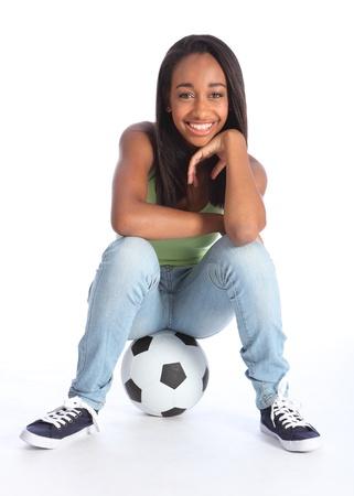Hermosa joven afroamericano ni�a adolescente de la escuela jugador de f�tbol, ??sentado en un bal�n de f�tbol relajante. Chica con pantalones vaqueros y un chaleco casual y tiene una sonrisa feliz.