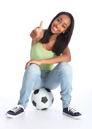 Football success for beautiful young African American teenage school girl soccer player, sitting on a ball with thumbs up sign. Girl wearing blue jeans and casual vest and has a big happy smile. photo
