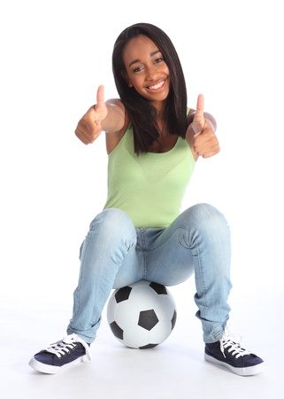 Football sports success for beautiful young African American teenage school girl soccer player, sitting on a ball with thumbs up sign. Girl wearing blue jeans and casual vest and has a big happy smile.