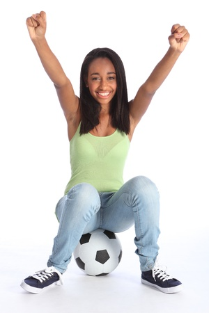 Football sports success for beautiful young African American teenage school girl soccer player, sitting on a ball with arms raised in triumph, with big happy smile. Stock Photo - 10429845