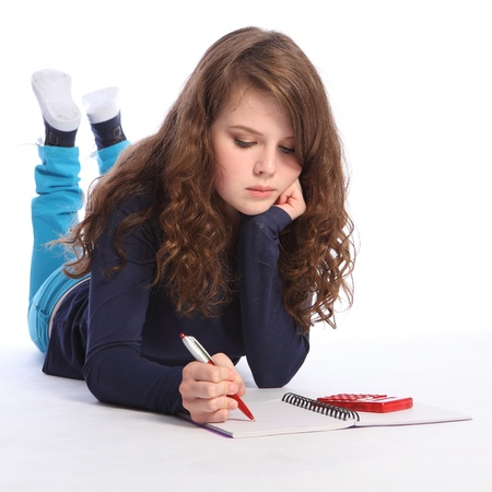 Teenager girl lying on floor doing her maths homework with a book, pen and calculator. Girl has long brown hair and is deep in concentration