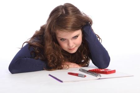 zapatos escolares: Chica adolescente confundido y alimentado hasta acostado en el piso haciendo sus deberes de matemáticas con una libreta, lápiz y calculadora. Chica tiene cabello largo castaño y viste una camisa azul de manga larga.