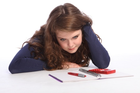 homework student: Confused and fed up teenager girl lying on floor doing her maths homework with a book, pen and calculator. Girl has long brown hair and is wearing a blue long sleeved shirt.