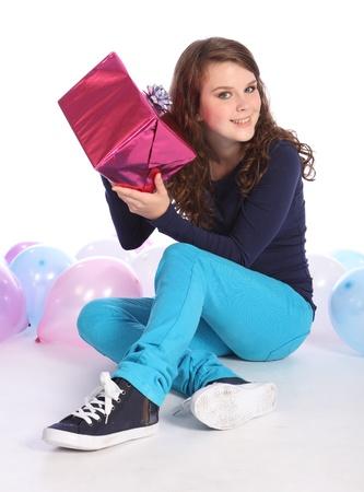 Chica adolescente hermosa con brillantes ojos azules celebra feliz ocasi�n con un regalo de cumplea�os sorpresa envuelta en papel de regalo color de rosa, sentado en medio de globos de fiesta.
