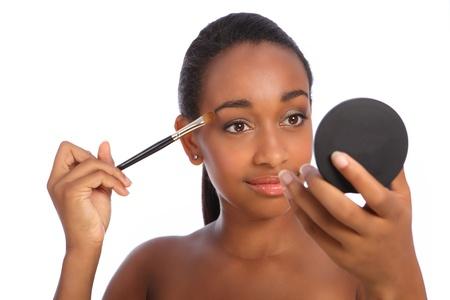 Joven y bella mujer afroamericana aplicar maquillaje utilizando una brocha de sombra de ojos con un espejo de cosm�tica compacta para obtener ayuda.