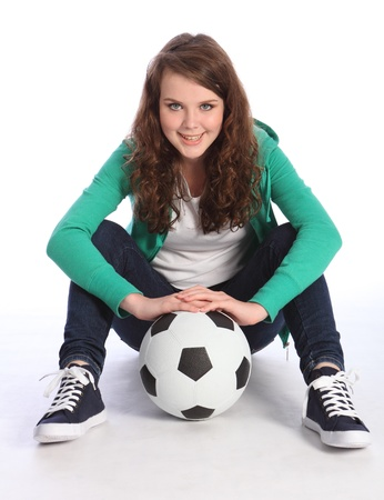 Cheerful teenage girl soccer player sitting on floor relaxing wearing green hoodie and blue jeans, holding football. photo